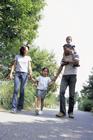 公園を散歩する4人家族