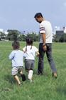 公園を歩く父親と子供2人