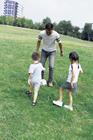 公園でサッカーで遊ぶ父親と子供2人