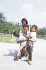 子供2人を抱き寄せる父親と家族4人