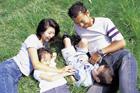芝生で寝転ぶ家族4人