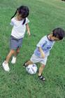 芝生でサッカーする子供2人