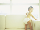 ソファでヨチヨチ歩きする赤ちゃん