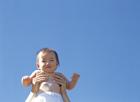 青空を背に抱えられる赤ちゃん