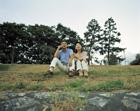 土手に座り空を見上げるミドルカップル