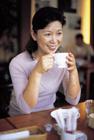 カフェでカップを持ちくつろぐミドル女性