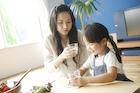 コップを持つ母親と女の子