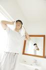 洗面所で髪を拭く30代男性