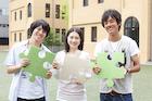 パズルピースを持つ3人の大学生