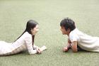 芝生で見つめあう若い男女