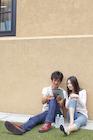 地面に座り電子端末を見る大学生カップル