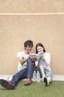 地面に座り教科書を見る大学生カップル