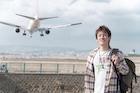空港で佇むリュックサックを背負った若い男性