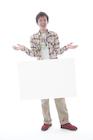 メッセージボードを宙に浮かす若い男性