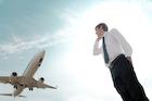 飛行機を背に電話するビジネスマン