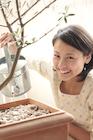 観葉植物の世話をする若い女性
