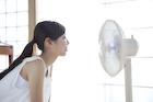 扇風機で涼む若い女性