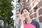 スポーツドリンクを頬にあてるジョギング姿の若い女性