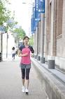 街中をジョギングする若い女性