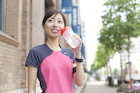 スポーツドリンクを持つジョギング姿の若い女性