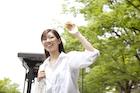 新緑の街で手を上げる若い女性