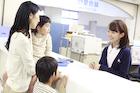 病院の受付で来院者に対応する女性職員