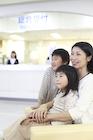病院の待合室で微笑む母親と子供2人