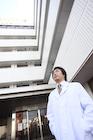 病院前で上を見上げる医師