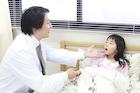 ベッドの女の子を診察する医師