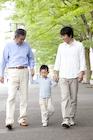 新緑の街を歩く男性3世代家族