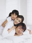 ベッドでくつろぐ家族3人