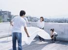 屋上で洗濯物を干す家族3人