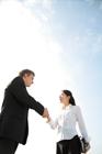 屋外で握手するビジネスマン男女
