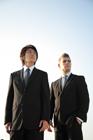 空を見上げる2人のビジネスマン