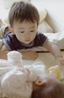 乳児に哺乳瓶をあたえる男の子