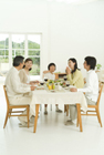 料理を頬張る女の子と食卓を囲む3世代家族5人