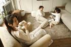 床で父と遊ぶ兄妹とお茶を飲む母