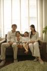 窓を背にソファで笑う家族4人