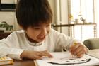 クレヨンで絵を書く左利きの男の子
