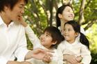 摘んだ花を手に新緑の公園でくつろぐ家族