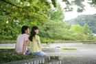 新緑の公園でくつろぐ大学生カップル