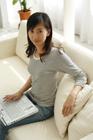 パソコンを膝に微笑む20代女性