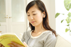 イヤホンで音楽を聴き読書する20代女性