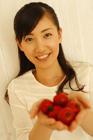 プチトマトを掌に微笑む20代女性