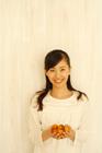 黄色のプチトマトを掌に微笑む20代女性