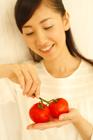 双子のトマトを掌に微笑む20代女性