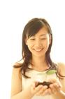双葉を掌に微笑む20代女性