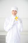 野菜を持って微笑む食品衛生服の女性