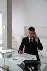 書類を前に電話するビジネスマン