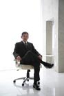 椅子に掛け足組みするビジネスマン